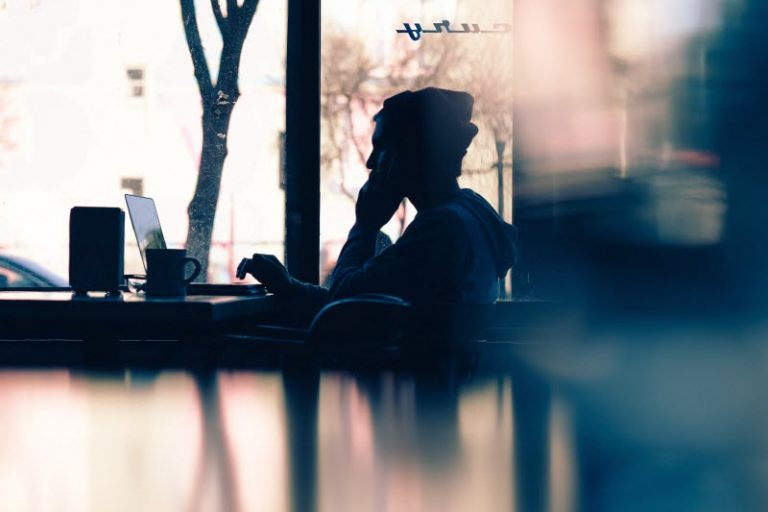 Woman seated at a cafe working on her side gig