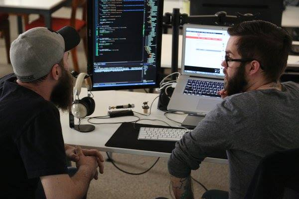 Two programmers at work on the computer