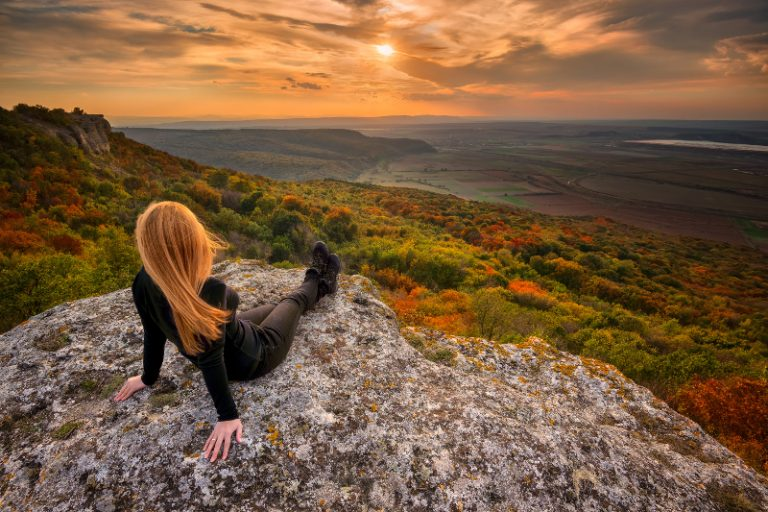 relaxed woman sitting on rock viewing the sunset