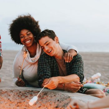 two friends roasting marsh mellows on the beach