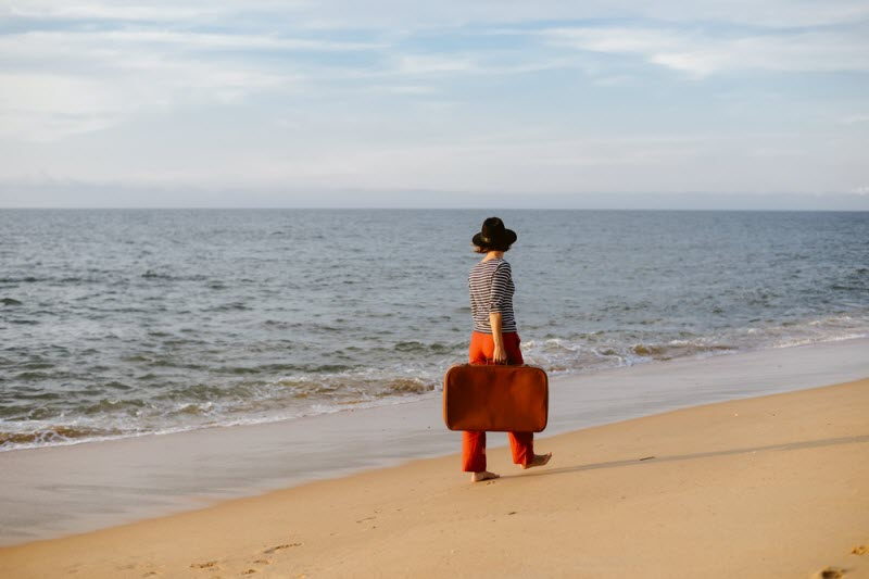 woman with a suitcase walking by the sea