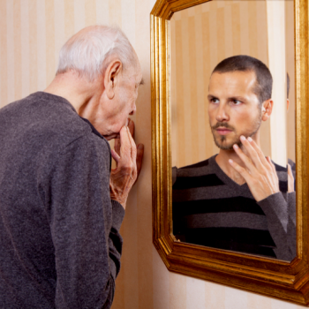 older man looking at his younger self in the mirror