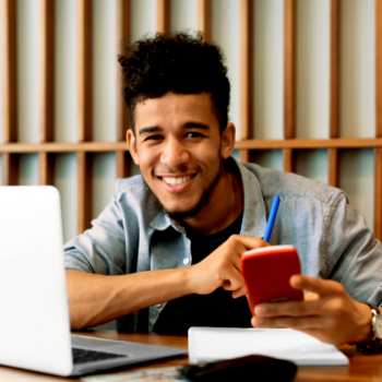 smiling young man with calculator and laptop