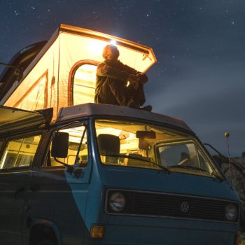 man sitting on VW bus looking at the stars