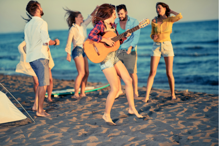 Young adults playing guitar and dancing on a beach start investing early