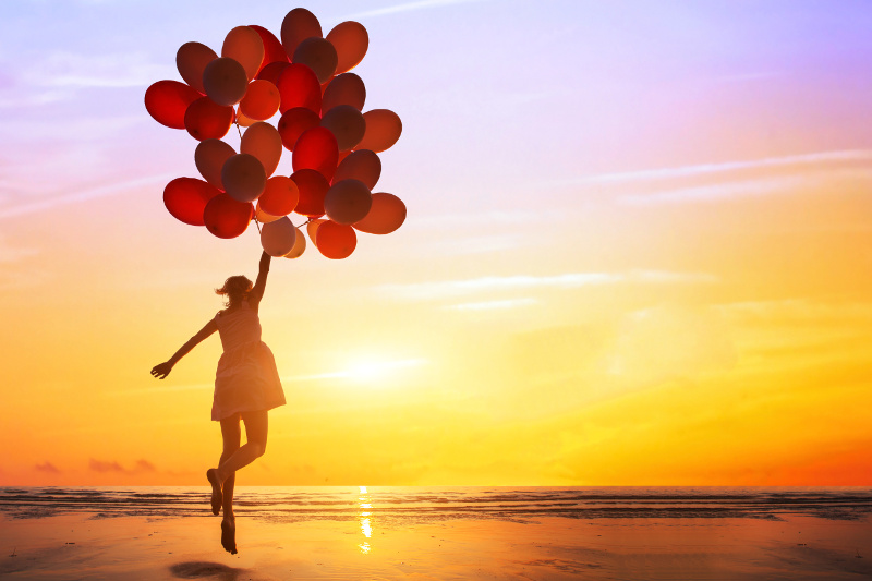 women lifted up by balloons on the beach in the sunset