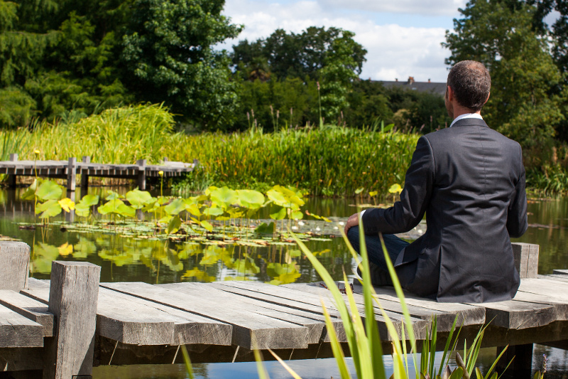 Business man meditating in Japanese garden