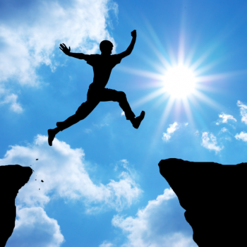 man leaping from one rock to another